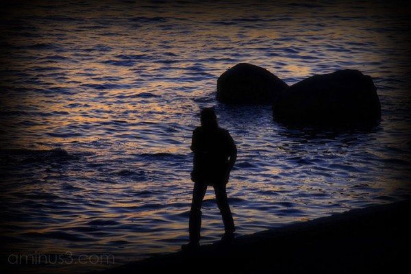 lone man walking agains sunset on water