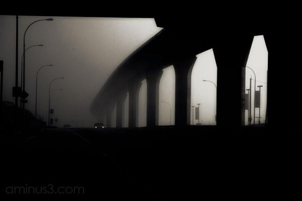 car traveling under trains rails in fog