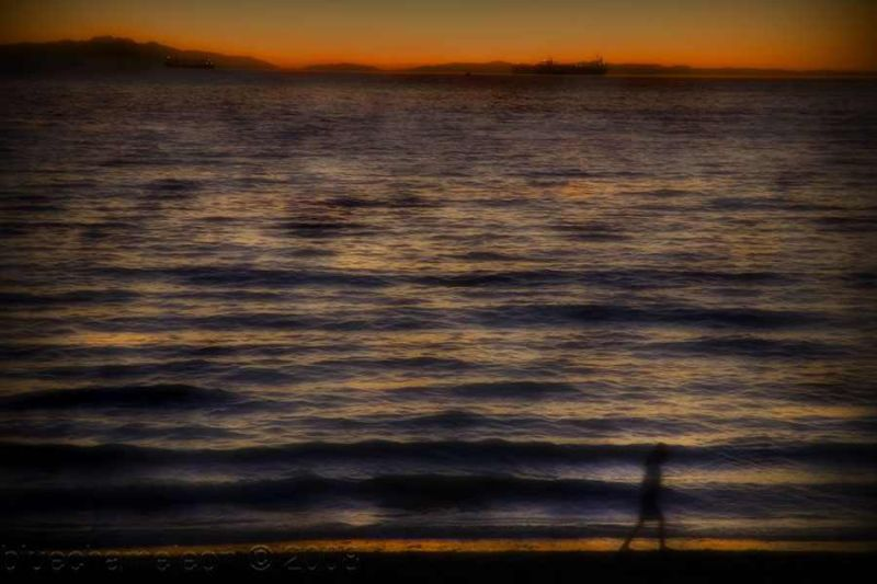 a spirit walking along the beach at sunset