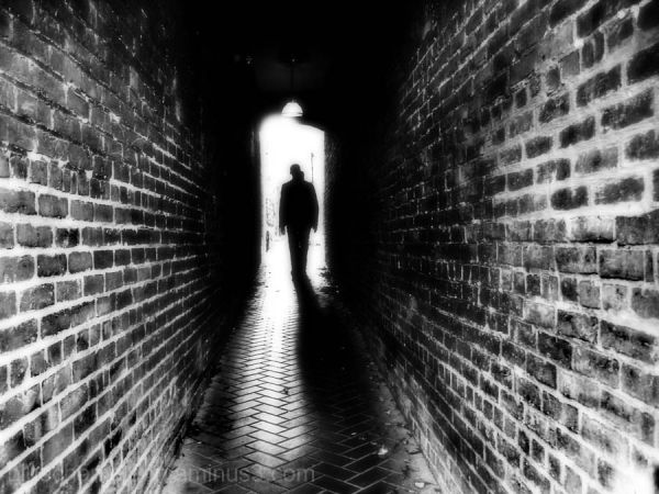 A 2 headed man walking between 2 walls into light
