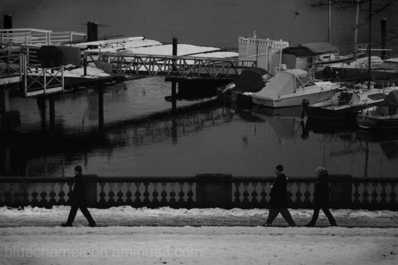 3 silhouetted people walking in snow, past marina.