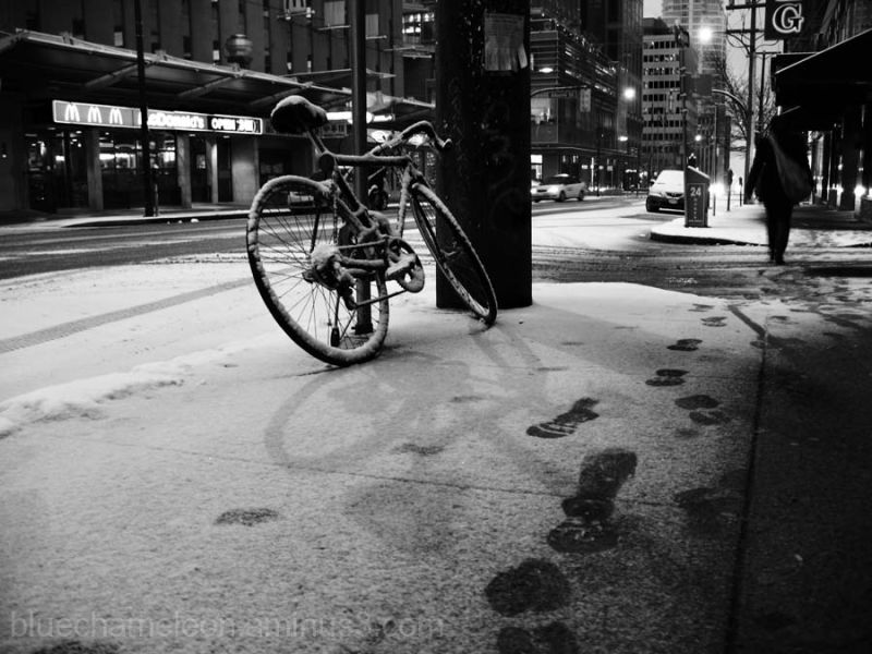 A snow covered bike on a city sidewalk in winter
