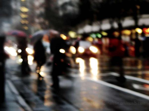 Blurred people walking in city light in rain