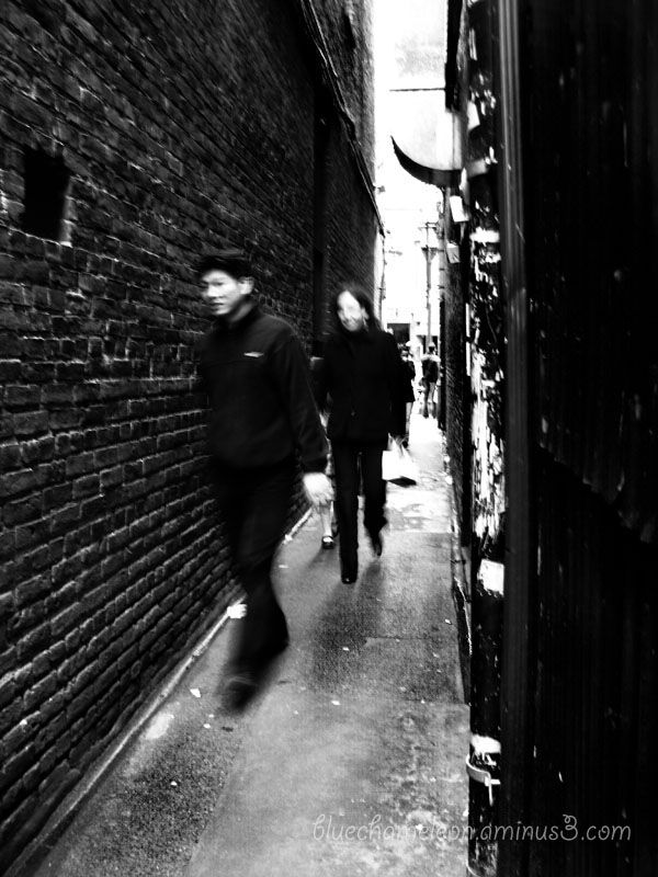 People rushing through a narrow alley in Chinatown