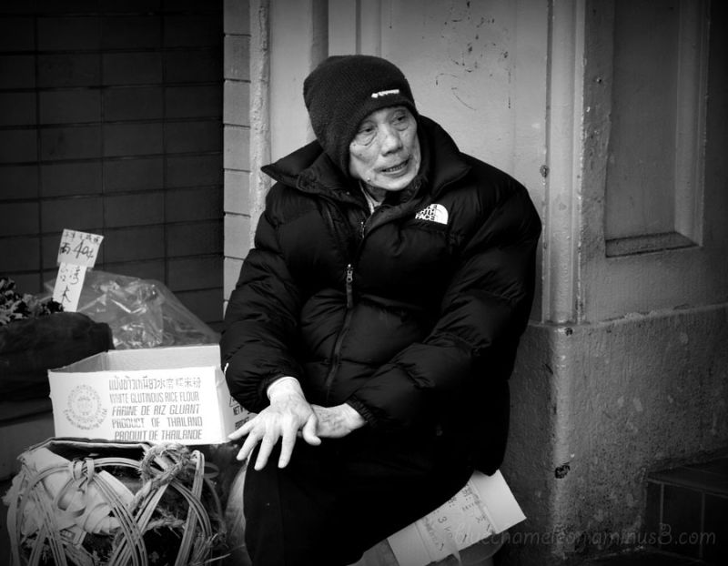 An old man sitting on a street corner in Chinatown