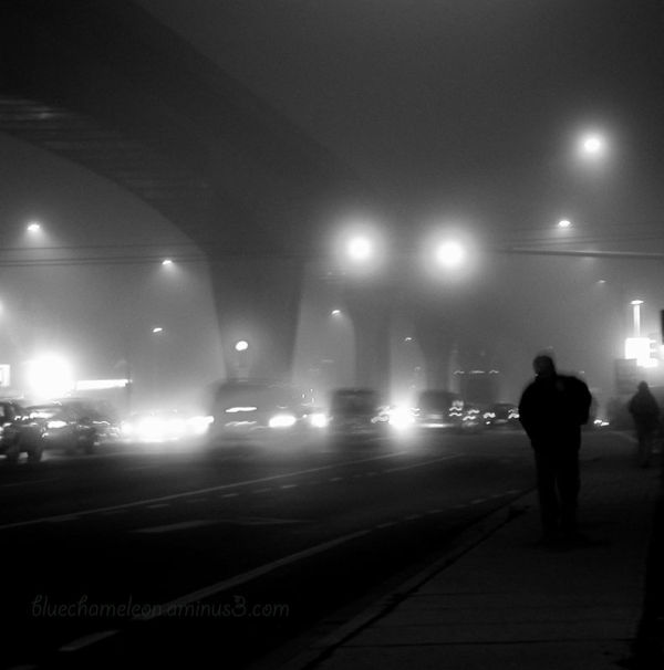 2 men walking along a foggy highway at night.