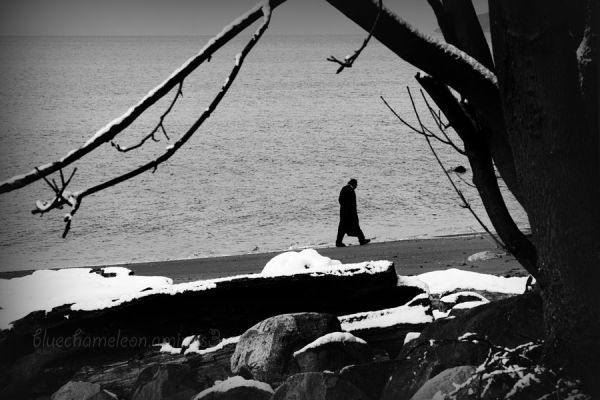 A man in a long coat walking along beach with snow