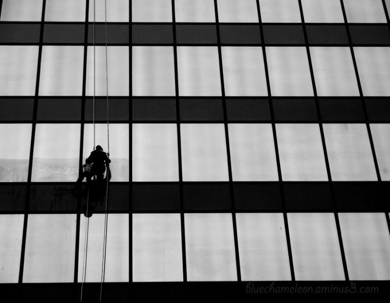 A man window washing up high on a skyscraper