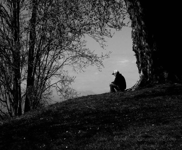 A lone man sitting alone at the top of a hill