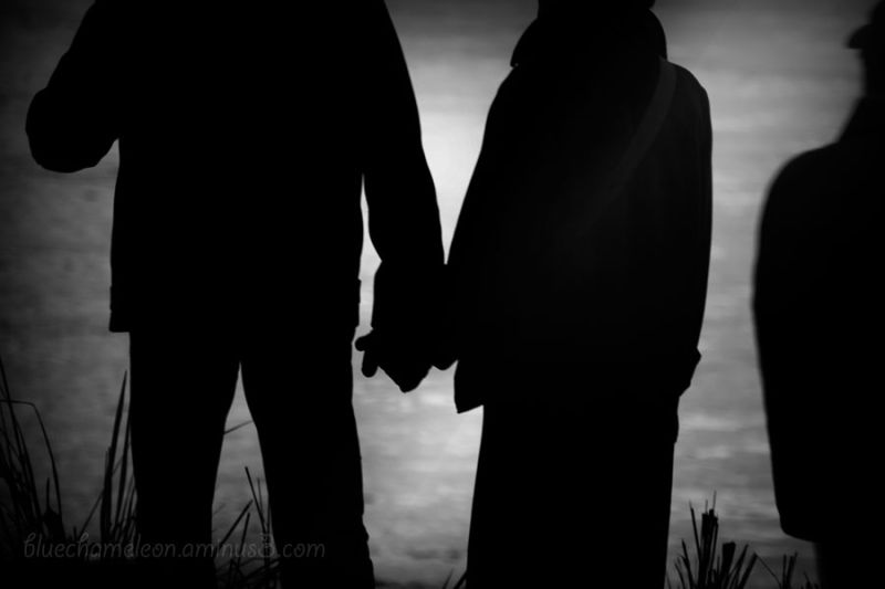A couple holding hands while lone man stands aside