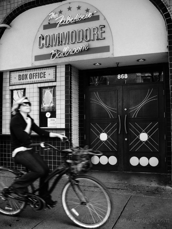 A woman riding bike past the Commodore Ballroom