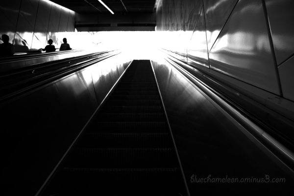 Bright light at top of escalator, people on left