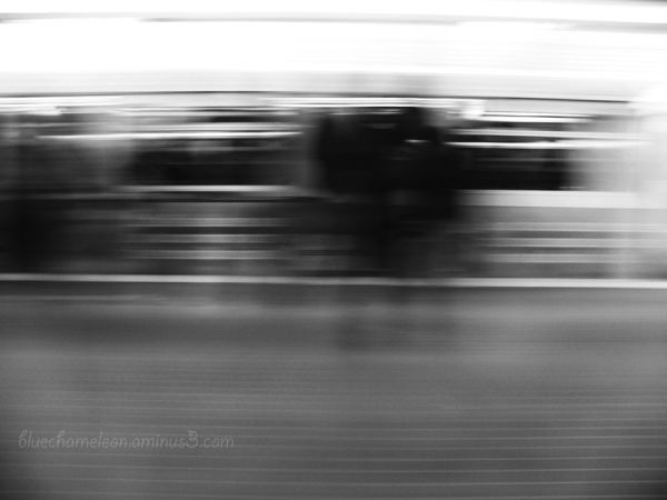 A blurred train with people waiting to get on it