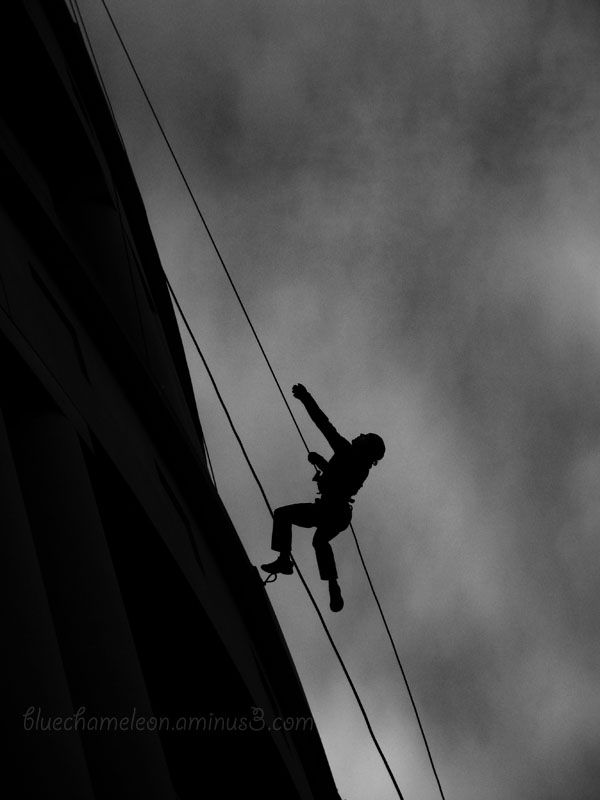 A silhouetted man hangs from wires at library