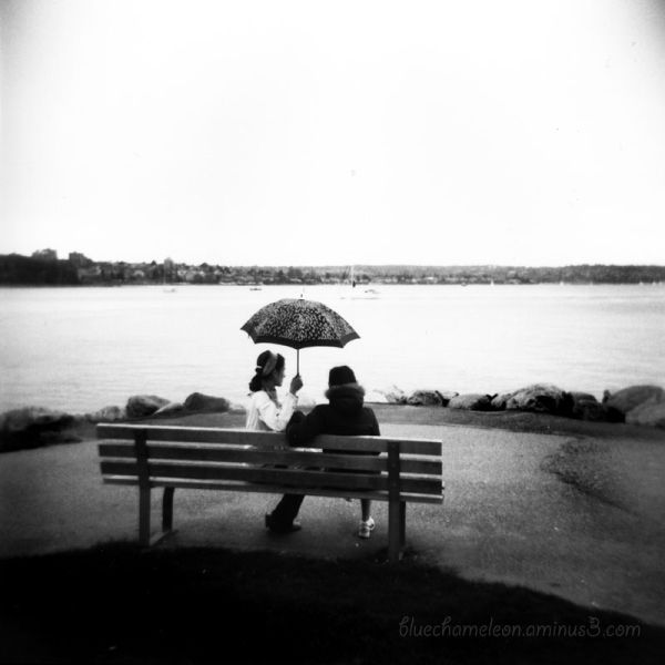 2 friends on bench at the ocean under an umbrella