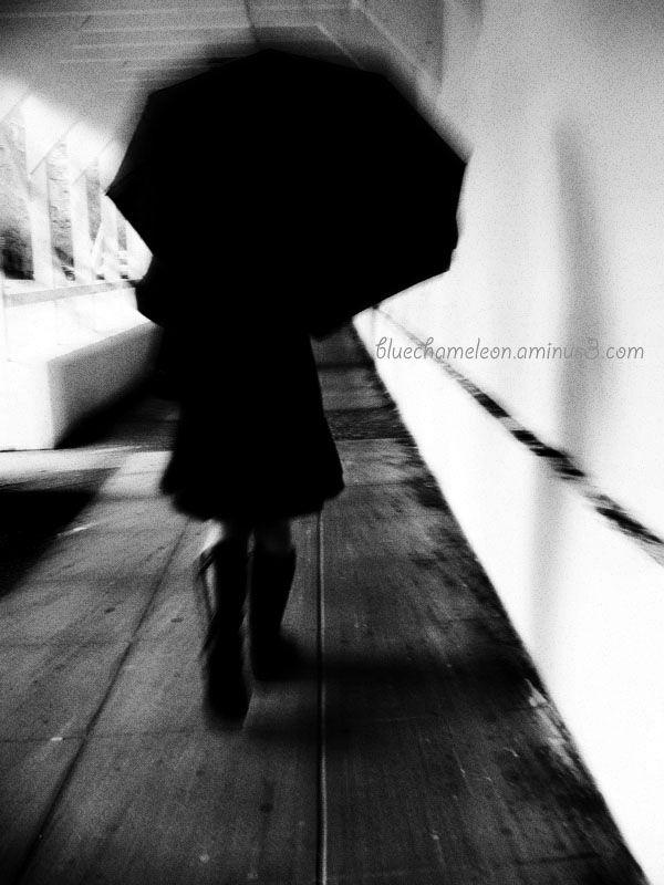 A woman with umbrella runs through scaffold tunnel