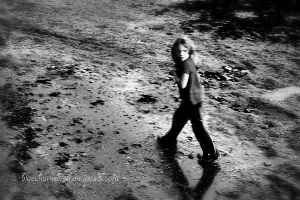 A young girl on the beach running scared.