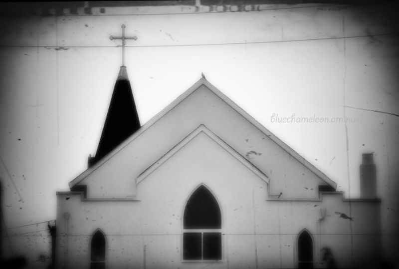 Old wood church with wires across & bird on roof