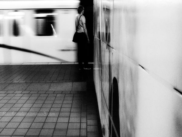 A man wait for a train going by in a blur