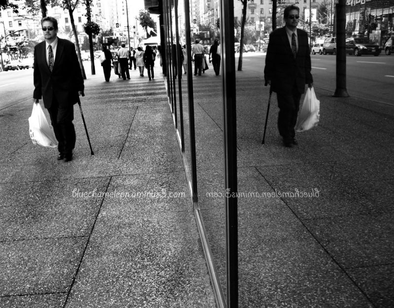 Man walking down street with reflection in window