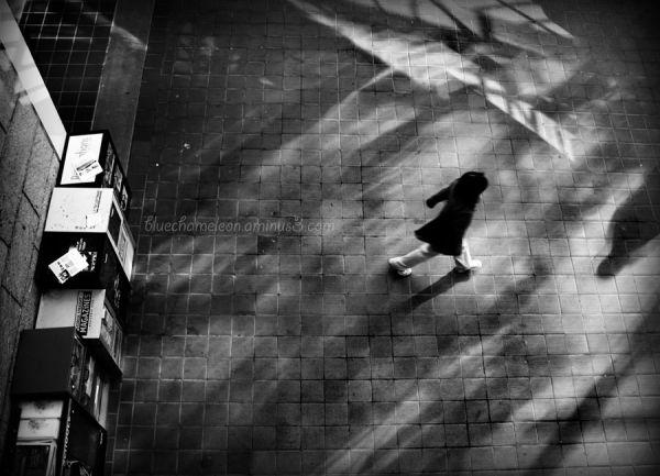 A woman running through ghostly shadows