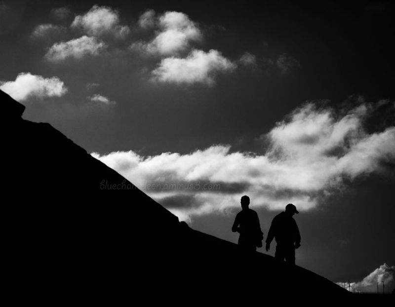 2 people walking along dark wall with clouds