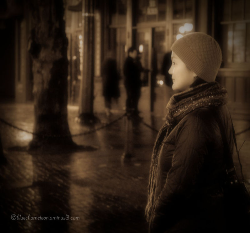 A woman on a wet city street at night