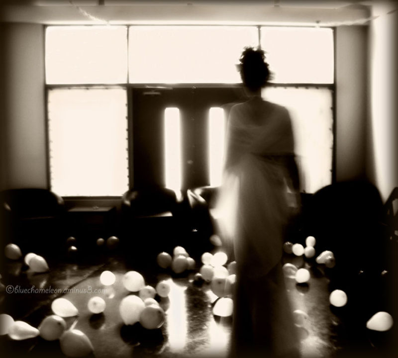 A blurred woman walking through balloons