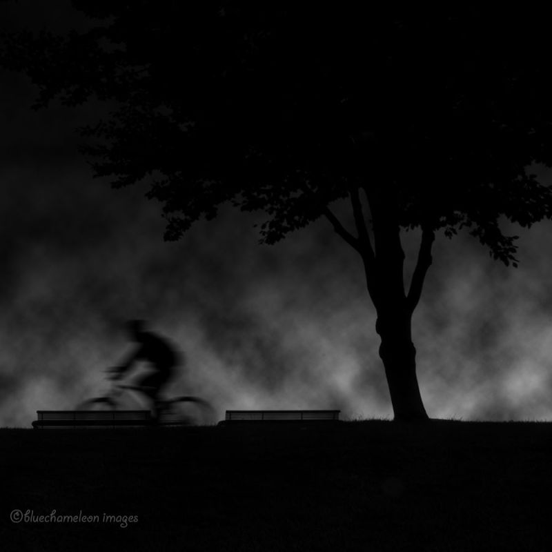 Bicyclist in motion riding through clouds at night