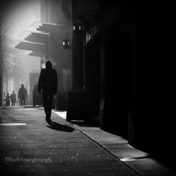 silhouetted people walking on street in fog