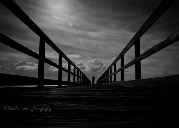 A silhouetted man standing on long pier, clouds
