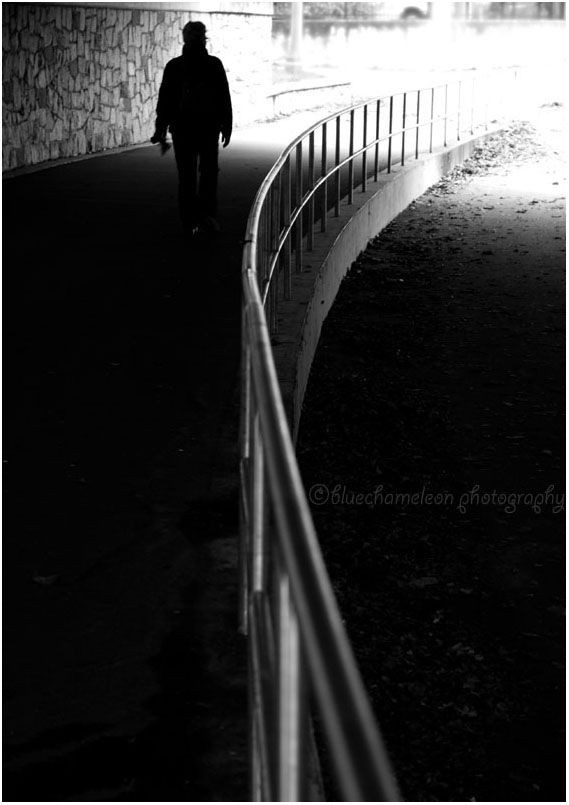 Silhouetted man walking by a curved rail leaves
