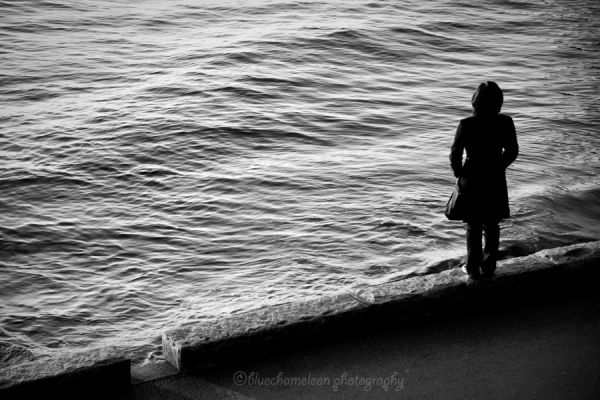 Silhouetted woman on path staring into the sea