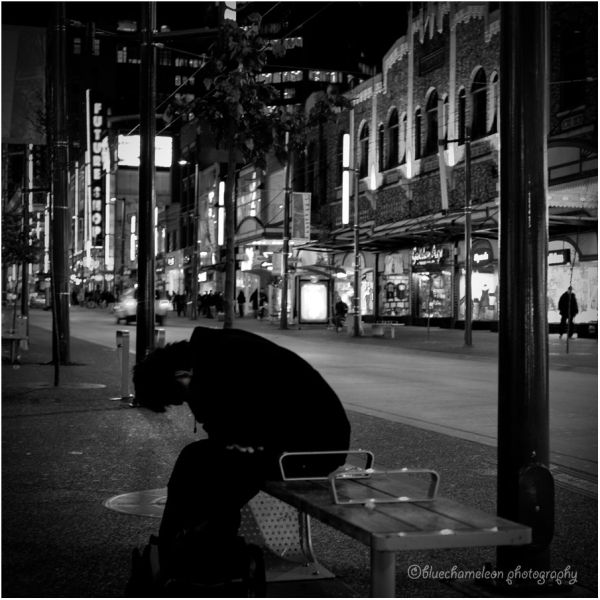 Silhouetted man sitting on city bench bent over
