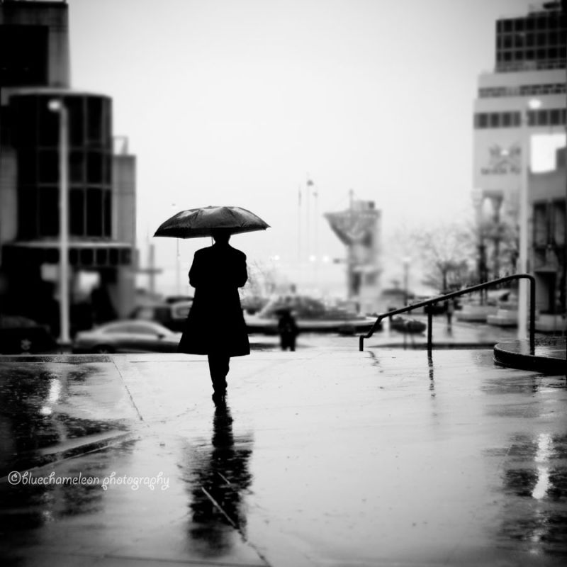 Lone man with umbrella walking through city