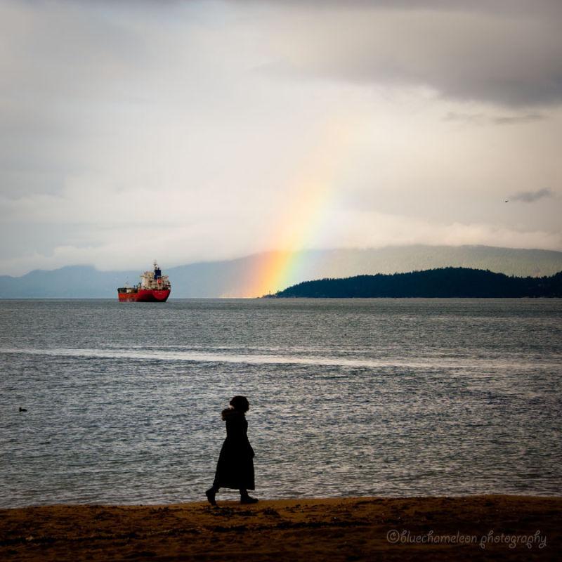 A woman walking along the beach with a rainbow