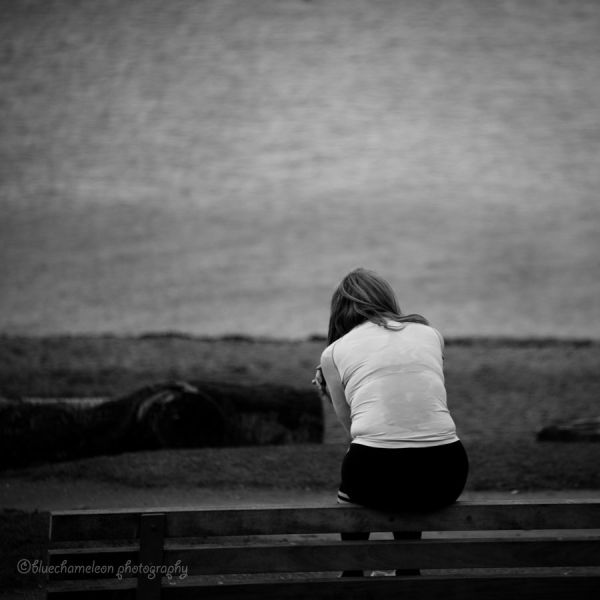 A woman slouched on bench, arms around herself
