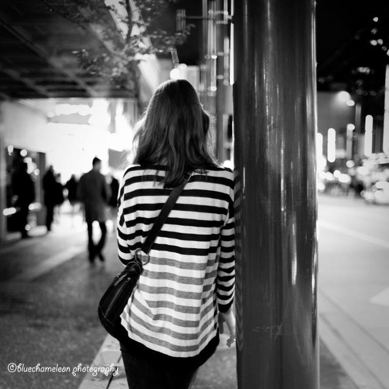 A woman in striped shirt standing on street