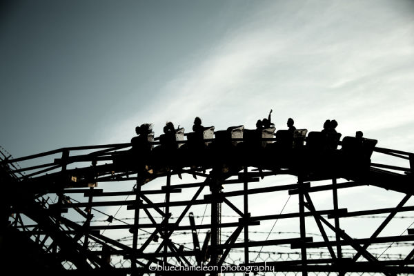 Silhouetted people riding a rollercoaster