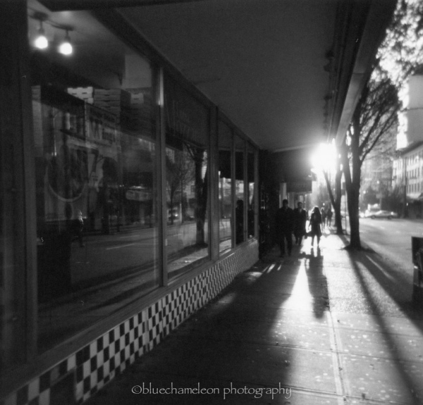 Backlit people on city street with long shadows