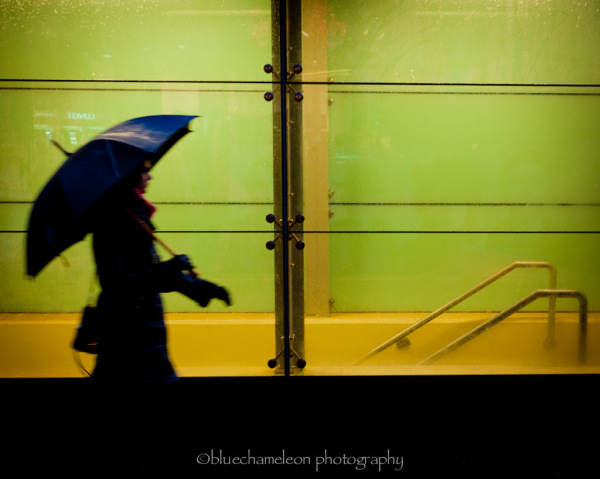 Silhouetted woman walking past window in rain