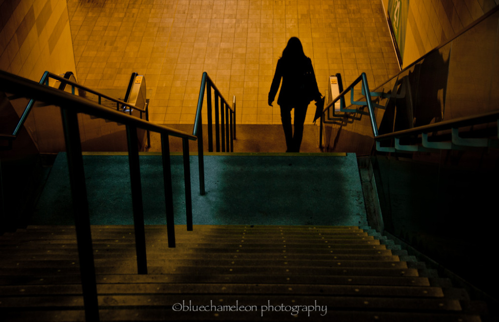 Silhouetted woman walking into train station