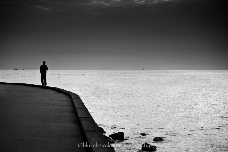 silhouetted man walking along seawall at sunset