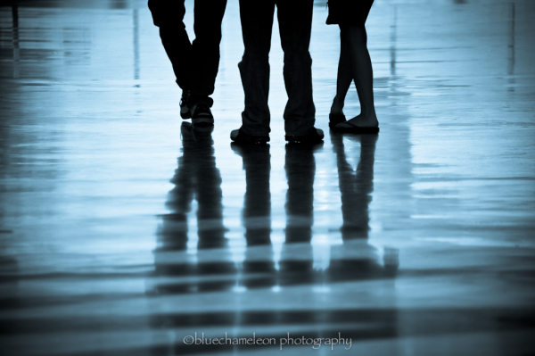 Silhouette and reflection of 3 people's legs