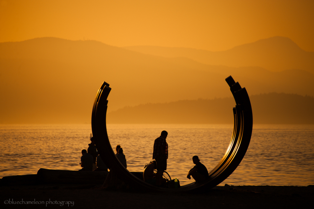 Silhouetted people and sculpture during sunset