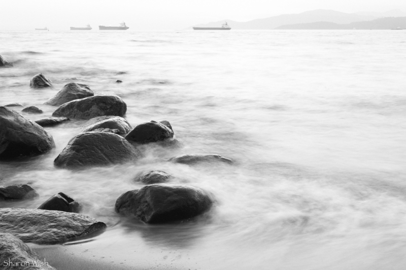 Misty ocean waves of rocks with ships on horizon