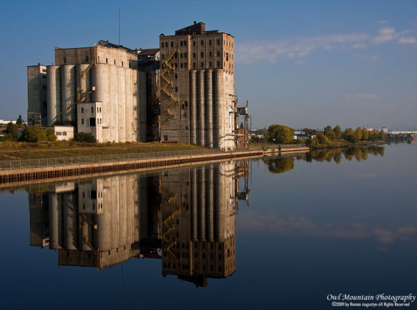 grain elevators reflected in water