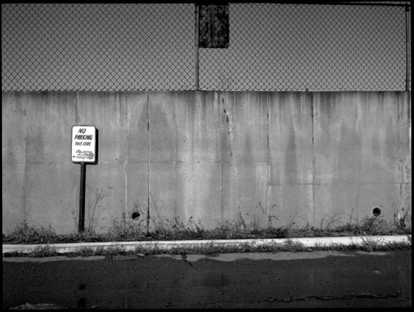 wall & fence, no parking sign - b&w photo