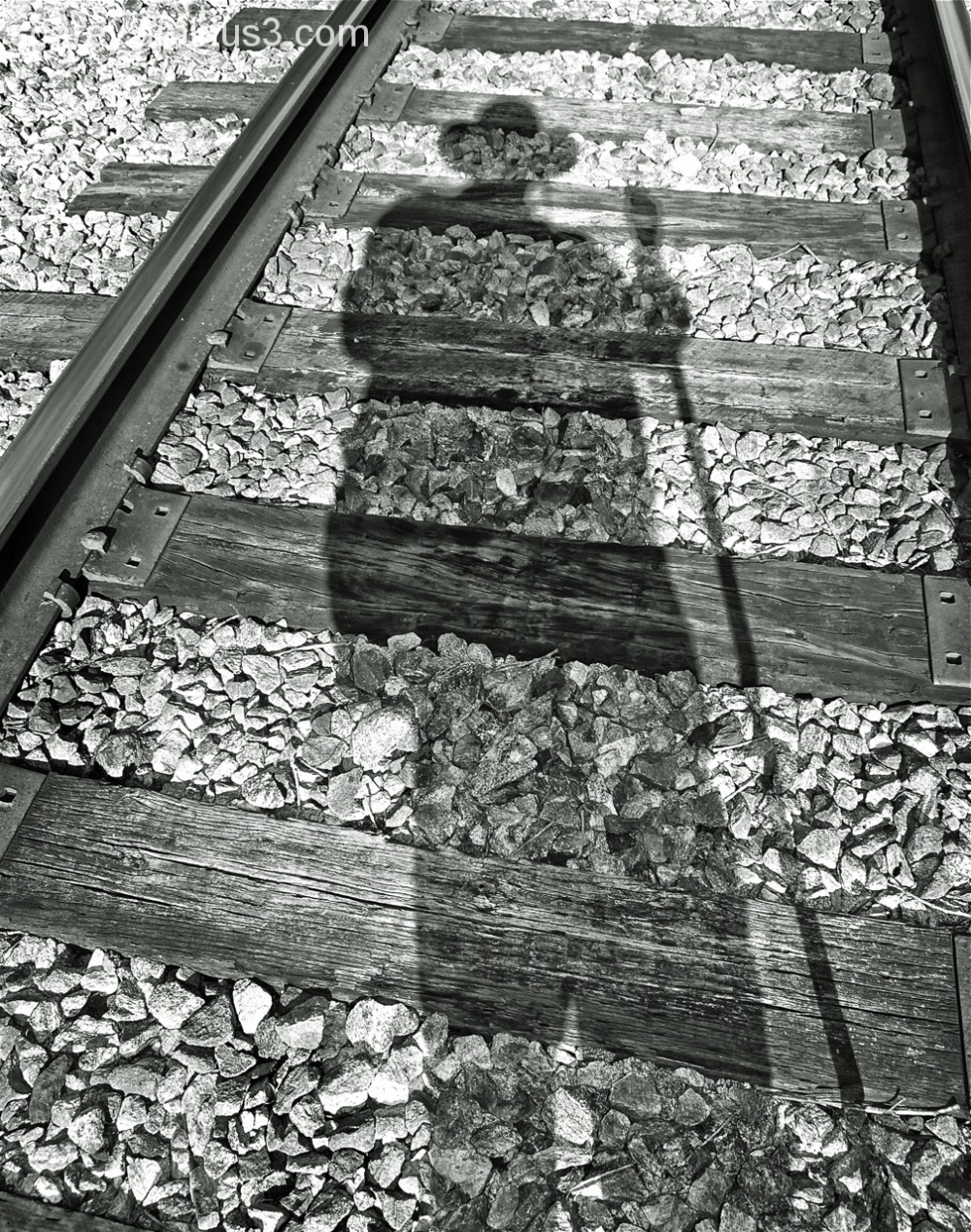 Shadow of self superimposed on train tracks