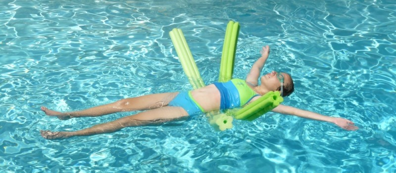 adolescent girl floats with noodles swimming pool